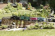 A g-scale train moves across a trestle in the front yard of Jerry and Lynne Humston during the open garden tour for garden railroad clubs from Cincinnati, Columbus and Indianapolis, Sunday, July 15, 2007.  Trains also fill most of the backyard.