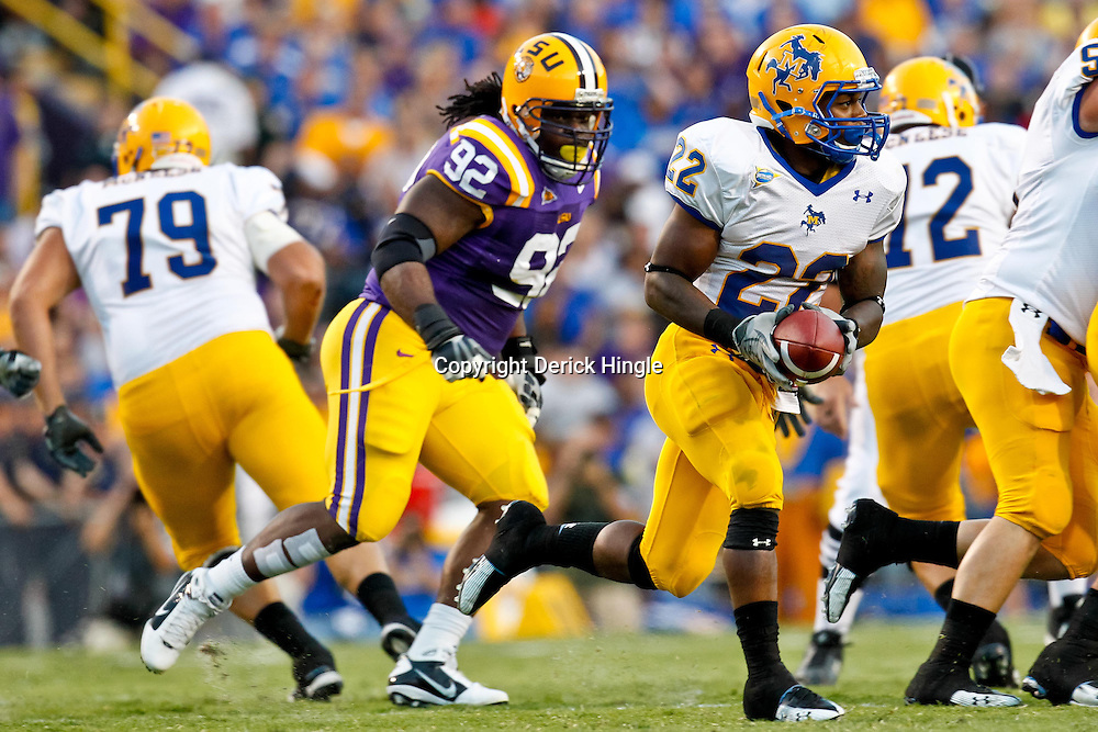 October 16, 2010; Baton Rouge, LA, USA; LSU Tigers defensive tackle Drake Nevis (92) pursues McNeese State Cowboys running back Andre Anderson (22) during the first half at Tiger Stadium.  Mandatory Credit: Derick E. Hingle