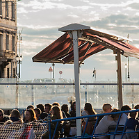 People enjoy the last sunrays having a drink in a bar on the Gran Canale in Trieste, Italy