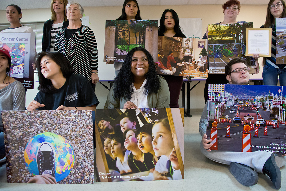 "mkb050617c/metro/Marla Brose --  Health Leadership High School students, including Kiara Williams, bottom center, hold their photographs from Pictures of Hope, a program that enables students to capture visions of their hopes and dreams through photography, ""My dream is to become a social worker,"" is printed on Williams' photograph. Carolyn Baca , who also was in the photo exhibition, was awarded with the Hope Scholarship, a full-ride scholarship to Blackburn College in Carlinville, Illinois, Tuesday, May 9, 2017. (Marla Brose/Albuquerque Journal)"