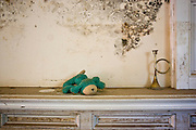 Children's stuffed toy and candle holder on a mantle of a home in the Lakeview area that suffered major damage due to Hurricane Katrina flooding in New Orleans, Louisiana. Many of these homes' interiors like this one remain untouched; floors are covered in flood debris and rubble while the walls and surfaces are still scab-covered layers of mold.