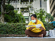 28 NOVEMBER 2014 - BANGKOK, THAILAND: A woman on the plaza in front of Siriraj Hospital prays for Bhumibol Adulyadej, the King of Thailand. The King was born on December 5, 1927, in Cambridge, Massachusetts. The family was in the United States because his father, Prince Mahidol, was studying Public Health at Harvard University. He has reigned since 1946 and is the world's currently reigning longest serving monarch and the longest serving monarch in Thai history. Bhumibol, who is in poor health, is revered by the Thai people. His birthday is a national holiday and is also celebrated as Father's Day. He is currently hospitalized in Siriraj Hospital, recovering from a series of health setbacks. Thousands of people come to the hospital every day to sign get well cards for the King. People wear yellow at events associated with the King because he was born on a Monday, and yellow is Monday's color in Thai culture. It's also the color of the monarchy.       PHOTO BY JACK KURTZ