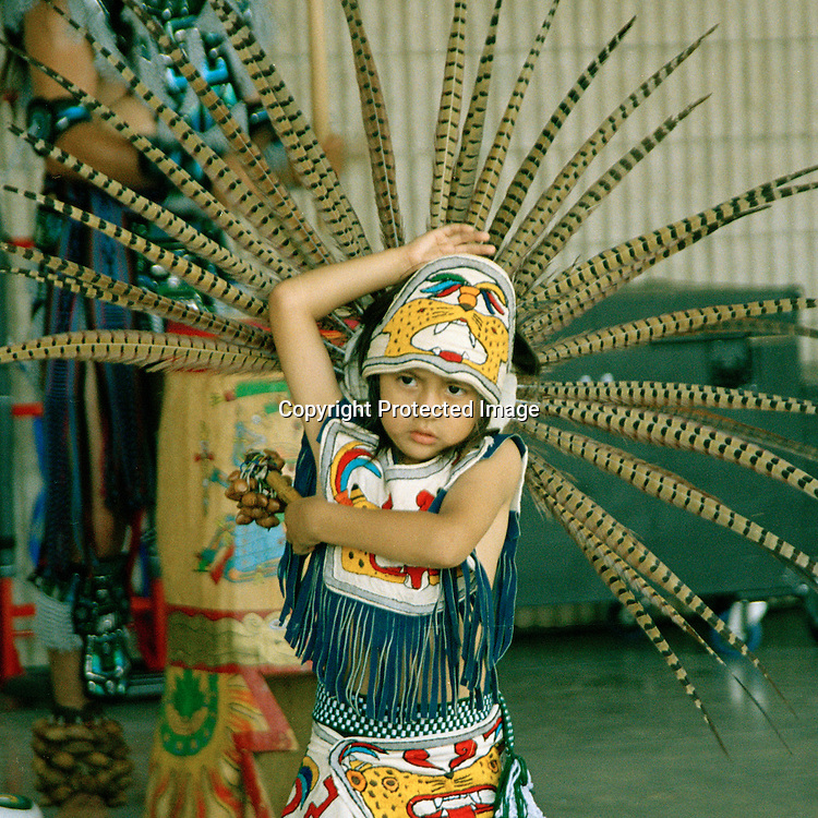 "Young dancer interprets traditional Aztec dance and dress at festival on the shore of Corpus Christi Bay. NOTE: Click ""Shopping Cart"" icon for available sizes and prices. If a ""Purchase this image"" screen opens, click arrow on it. Doing so does not constitute making a purchase. To purchase, additional steps are required."