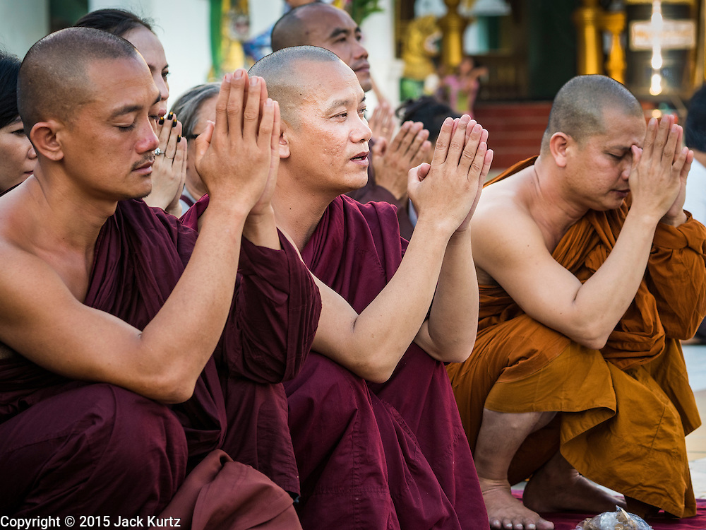 31 OCTOBER 2015 - YANGON, MYANMAR: Burmese Buddhist monks lead prayers at Shwedagon Pagoda. Some members of the Burmese Sangha (brotherhood of monks) have inserted themselves into Myanmar's election campaign. Members of Ma Ba Tha, an organization of nationalist conservative monks, have come out in opposition to Aung San Suu Kyi and her National League for Democracy (NLD), saying she is too friendly with Myanmar's Muslim minority and would not be able to govern Myanmar. Shwedagon Pagoda is officially known as Shwedagon Zedi Daw and is also called the Great Dagon Pagoda or the Golden Pagoda. It is a 99 metres (325 ft) tall pagoda and stupa located in Yangon, Burma. The pagoda lies to the west of on Singuttara Hill, and dominates the skyline of the city. It is the most sacred Buddhist pagoda in Myanmar and contains relics of four past Buddhas: the staff of Kakusandha, the water filter of Koṇāgamana, a piece of the robe of Kassapa and eight strands of hair from Gautama, the historical Buddha. The pagoda was built between the 6th and 10th centuries by the Mon people, who used to dominate the area around what is now Yangon (Rangoon). The pagoda has been renovated numerous times through the centuries. Millions of Burmese and tens of thousands of tourists visit the pagoda every year, which is the most visited site in Yangon.      PHOTO BY JACK KURTZ