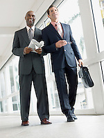 Two businessmen walking in hallway (low angle view)