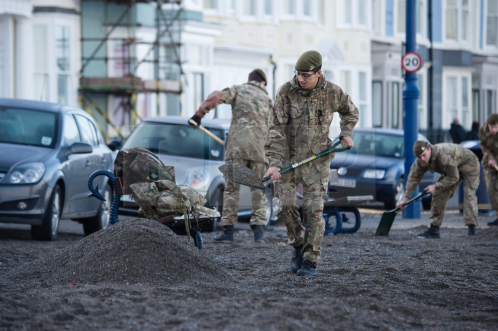 © Licensed to London News Pictures. 16/02/2014. Aberystwyth, UK Over 30 young soldiers, members of the Wales Officers Training Corps based at Aberystwyth University, gave up their sunday morning lie-ins to volunteer to clean the promenade at Aberystwyth on the west wales coast. Photo credit : Keith Morris/LNP