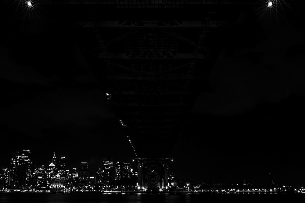 The Sydney Harbour Bridge spanning across Sydney Harbour with a view to the city at night.