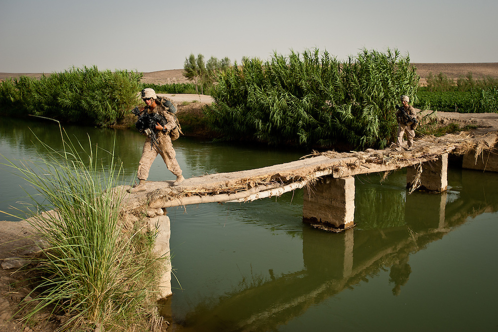 A Marine crosses a narrow bridge over an irrigation canal in Marjah. In the 1950s, Marjah the site of a major U.S.-led agricultural project. These days, the canals are the only remnant of the earlier U.S. project.