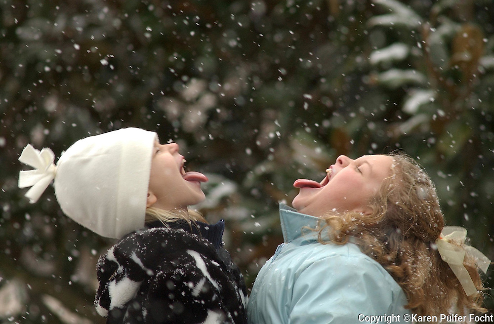 Snow Flakes: Caroline Hughes,9, and Kimberly Gibson (rt) catch snow flakes on their tounges during Sunday afternoons snow. The girls enjoyed playing in their Chickasaw Gardens neighborhood.