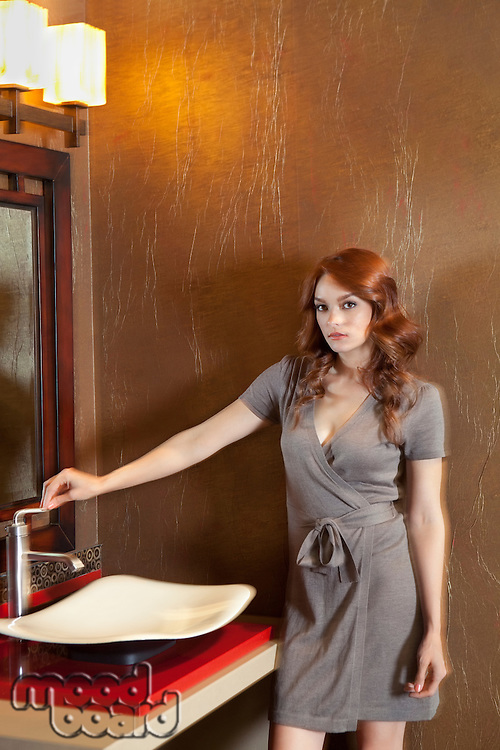 Portrait of beautiful young woman standing near sink in model home