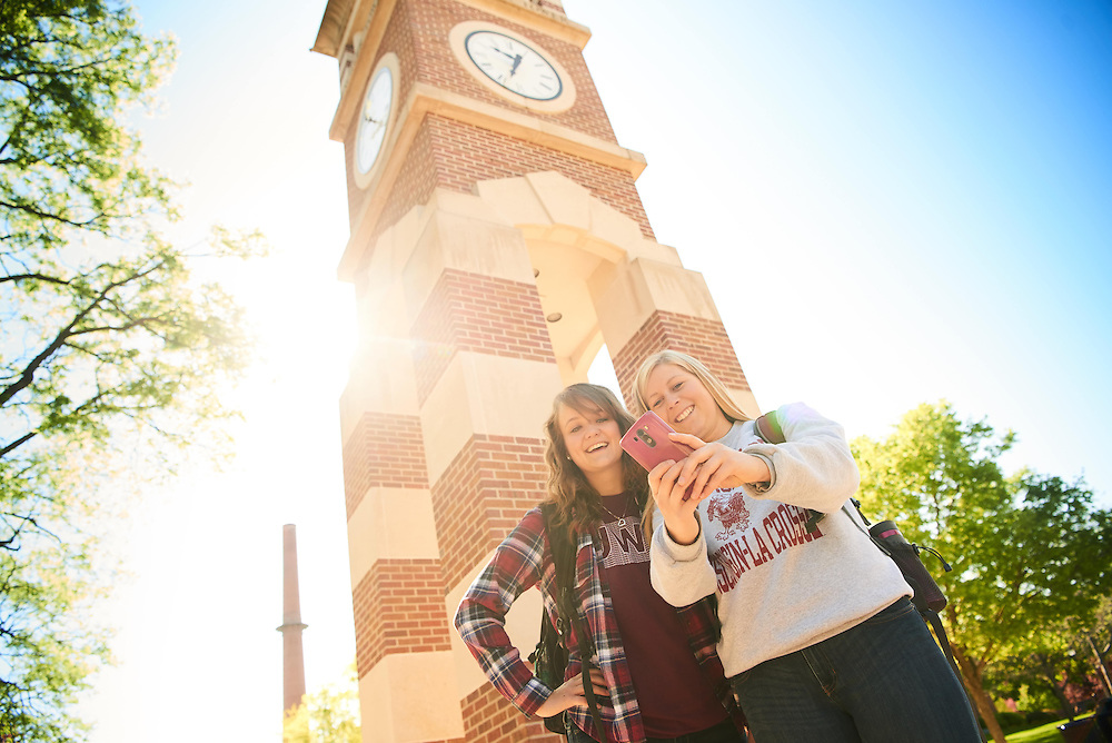 Activity; Relaxing; Socializing; Smiling; Buildings; Clock Hoeschler Tower; Location; Outside; Objects; Phone Cell Smartphone iPhone; People; Woman Women; Student Students; Spring; May; Type of Photography; Candid; Time/Weather; sunny; UWL UW-L UW-La Crosse University of Wisconsin-La Crosse; Lifestyle; selfie; Katie Eisenhauer; Emma Hermes