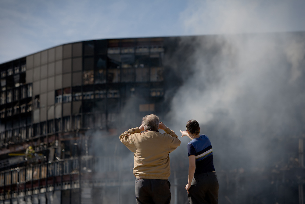 Bob Binder, left, and daughter Margeaux Binder, right, watch as emergency crews extinguish a fire at the Echelon I building in north Austin after a plane crash on February 18, 2010.  Joseph Stack wrote a 3,000 word anti-government manifesto and set his own house on fire before driving to a Georgetown airport where he flew his Piper Dakota plane less than 30 miles to the building that housed local offices of the IRS.