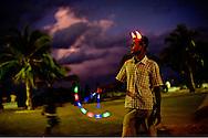 En mand sælger lyslegetøj på promonaden i Male. Han sælger også horn i panden som djævlen. Klimaforandringerne kan få store dele af Maldiverne til at forsvinde. Maldiverne, der ligger ud for Indiens sydspids, er et af de lande i verden, der er mest truet af klimaforandringerne og stigningen i havenes vandstand. FN skønner, at store dele af Maldiverne vil være forsvundet i 2100. Der bor 350.000 mennesker på Maldiverne. Det højeste punkt for de 1190 koraløer er 2,4 meter over havets overflade.