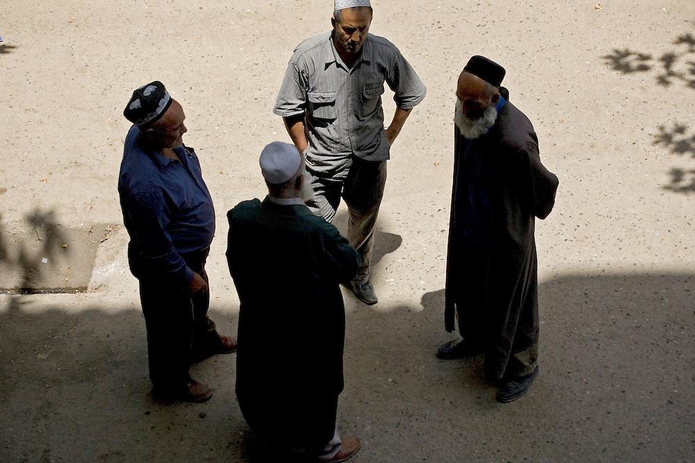 Men in traditional Muslim dress, talking in market, Dushanbe