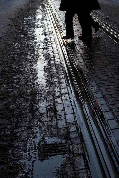 Man crosses muddy tram rails on Leidsestraat, Amsterdam, December 2010