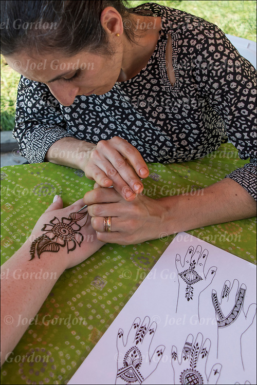 Henna design tattoo by Mangala Buhler-Rose in Washington Square Park at the Hare Krishna Festival of Chariots. <br /> <br /> You can find Mangala at mehndinyc@gmail.com and mehndinyc.com.<br /> <br /> Henna is a temporary tattoo non-permanent image on the comes from south Asian and India. The paste is made from the powdered leaves of the Henna plant,  traditionally it is drawn in delicate patterns on the hands and feet.  <br /> <br /> Henna is regarded as having &quot;Barakah,&quot; blessings, and is applied for luck as well as joy and beauty.