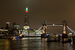 © Licensed to London News Pictures. 14/12/2015. London, UK.  The London Shard is lit up in alternating festive red, green and white colours during the run up to Christmas and seen here next to Tower Bridge on the River Thames. Photo credit : Vickie Flores/LNP