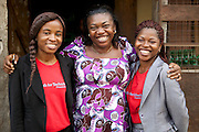 Peace (right) and Ifeoma (left) from Youth for Technology pictured here with Ojiugi Ogbuji.<br /> <br /> Ojiugi Ogbuji started her business in 2000, beginning with door to door sales of baby items. <br /> <br /> She later expanded into the unit next door and started selling soft drinks and water too. <br /> <br /> She attended the Youth for Technology business training first and then heard about the business advice SMS service. <br /> <br /> The main thing she learnt from the training was about the importance of eye-catching displays to attract people into the shop and also the value of loans.