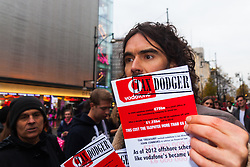 "Oxford Street, London, December 5th 2014. Actor and Comdeian turned political activist Russel Brand visits several big brands'  stores including Boots, Apple and Vodafone in London accusing them of dodging tax whilst those most in need of benefits are facing cuts and increased hardship. A leaflet being distributed by him claims £14 billion is lost every year, through tax avoidance and loopholes exploited by big business. PICTURED: Comedian Russel Brand distributes leaflets accusing Vodafone of deing a ""Tax Dodger""."