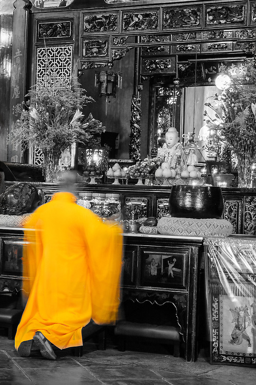 Long exposure image of a Taoist monk praying at the altar in Melaka, Malaysia.