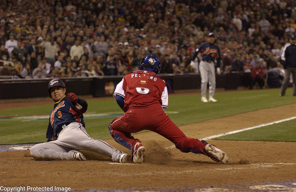 Team Japan's Nobuhiko Matsunaka slides home safe in the 9th inning against Team Cuba in Final action of the World Baseball Classic at PETCO Park, San Diego, CA.