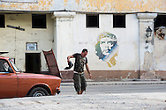 "A man shakes out a rag while working on a mechanical problem with his car in Cuba's Habana Vieja. In the background in a mural of Ernesto ""Che"" Guevara."