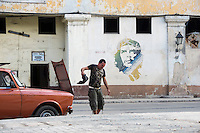 """A man shakes out a rag while working on a mechanical problem with his car in Cuba's Habana Vieja. In the background in a mural of Ernesto """"Che"""" Guevara."""