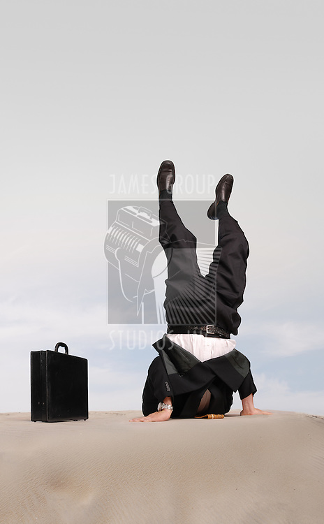 Businessman standing on his head with his head in the sand