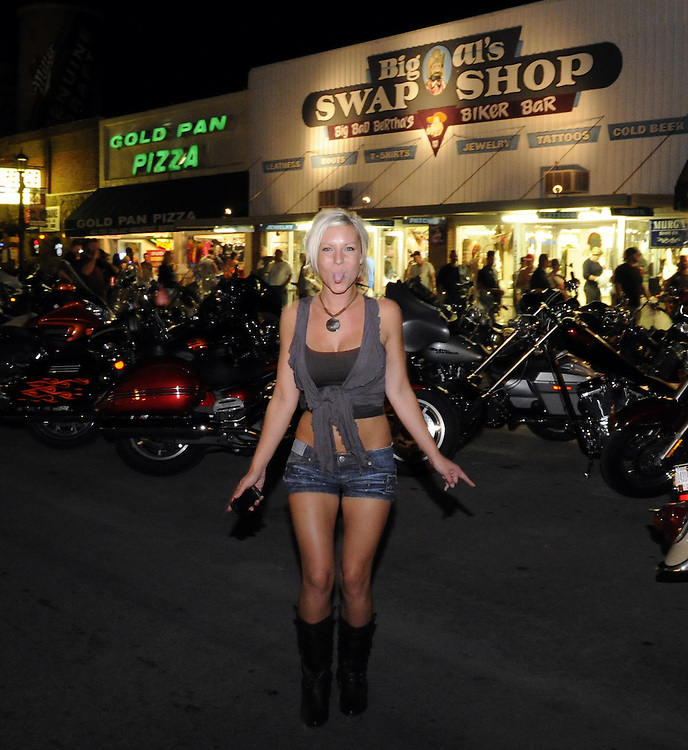 STURGIS, SOUTH DAKOTA - AUGUST 2010:  A young lady has fun while on Main Street in downtown Sturgis, South Dakota during the 70th annual Sturgis Motorcycle Rally held in the Black Hills.  The attendance estimates were placed between 500, 000 and 700,000 bikers.