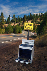 """A highway sign indicating """"Open Range"""" warning motorist of livestock has an open oven range placed in front of it advertising a local B&B on OR Rt 66, near Ashland, Oregon"""