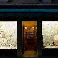 Italy, Veneto, Venice. November/12/2007...A linen shop facade lit up at dusk in Venice, Italy.