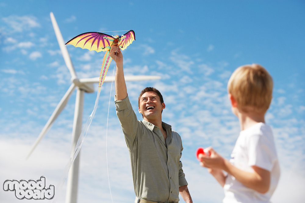 Father and son (7-9) playing with kite at wind farm