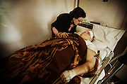 """March 23, 2012 , Damascus , Syria : Violette Diab- 66-  with her husband Samir Saad 72 year old , at the French hospital in Damascus , Samir injured due an explosion targeted his neighborhood Kassa'a on March 17 , 2012 . Violette recounts how they survived """" Usually, Samir wakes up and prepares coffee for the two of us. On the day of the explosion, I was in bed half asleep waiting for Samir to announce coffee time. Suddenly, I heard a huge explosion that shook the whole room and all the mirrors in the closet shattered on me. I hid myself beneath the cover. Then I started crawling to look for Samir. The floor was full of glass. I found him laying on the floor with the TV, the wall, and glass pieces all over him. He laid there still. I started screaming, Samir is dead! Samir is dead! Then out of nowhere, I see two young men enter the house and carry Samir in a blanket to the French hospital in our neighborhood. I thank God Samir made it. It was a miracle. Now he is doing better though he has lost sight in his right eye and his hearing is damaged. As soon as he woke up, he asked me about what happened. I told him that a bomb blew up the security building, He asked, what kind of an explosion would do this to me??"""