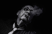 black and white portrait of man smoking against black background