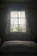 early morning light streaming through a window bed in the foreground