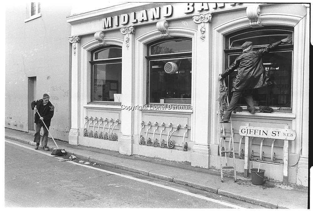 Street sweeper and man cleaning window of Midland Bank, South-East London, London street photography in 1982. Tri-X