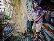 "29 DECEMBER 2018 - BANGKOK, THAILAND: A man stretches longevity noodles during the drying process in front of his family shophouse. The family has been making traditional ""mee sua"" noodles, also called ""longevity noodles"" for three generations in their home in central Bangkok. They use a recipe brought to Thailand from China. Longevity noodles are thought to contribute to a long and healthy life and  are served on special occasions, especially Chinese New Year, which is February 4, 2019. These noodles were being made for Chinese New Year.    PHOTO BY JACK KURTZ"