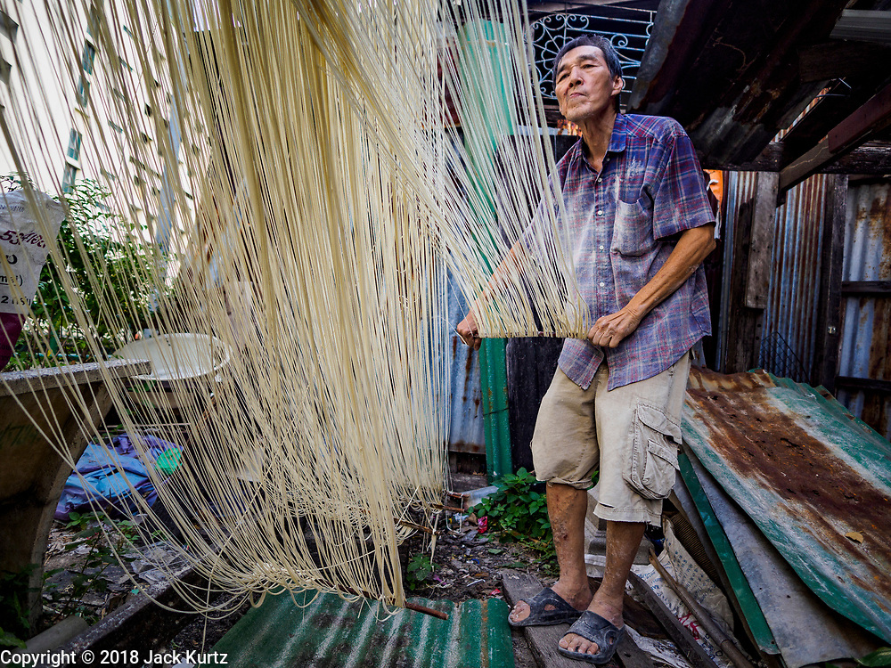 """29 DECEMBER 2018 - BANGKOK, THAILAND: A man stretches longevity noodles during the drying process in front of his family shophouse. The family has been making traditional """"mee sua"""" noodles, also called """"longevity noodles"""" for three generations in their home in central Bangkok. They use a recipe brought to Thailand from China. Longevity noodles are thought to contribute to a long and healthy life and  are served on special occasions, especially Chinese New Year, which is February 4, 2019. These noodles were being made for Chinese New Year.    PHOTO BY JACK KURTZ"""