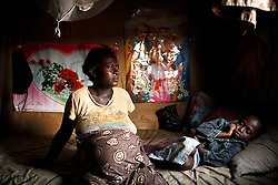 Salimatu, 8 months pregnant with her son at home in the slum Kroo Bay. Salimnatu grew up in this area, and remembers when it was a green rice growing area with a few fishermen. Salimatu worried for her unborn child, she has alreayd lost a child. Kroo Bay, Freetown, Sierra Leone.