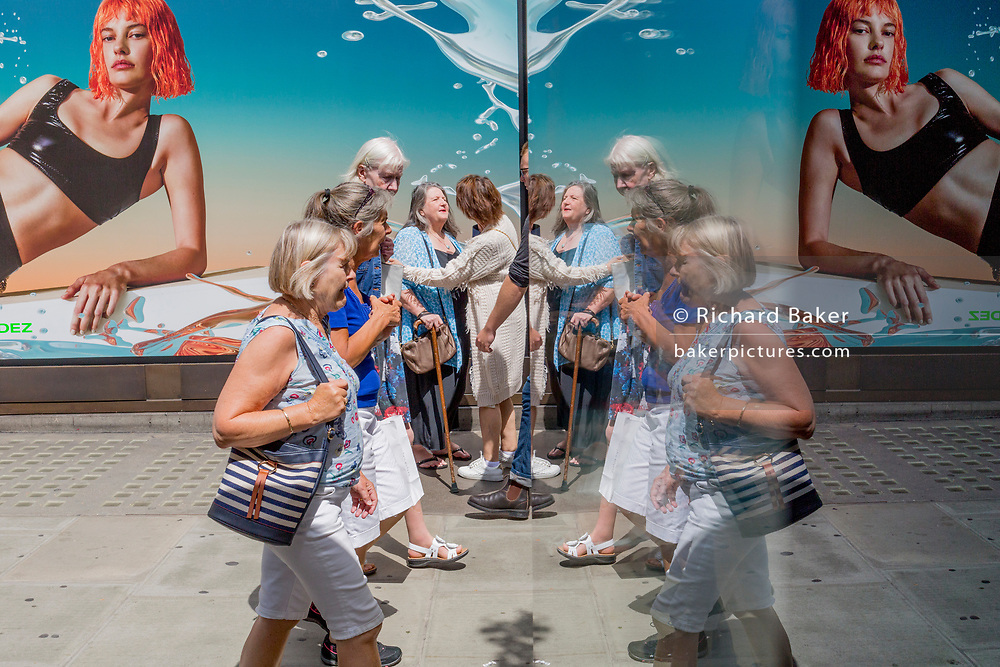 Middle-aged shoppers walk past a female model in an advert outside the London location of the Selfridges Department store on Oxford Street, on 2nd July 2019, in London, England.