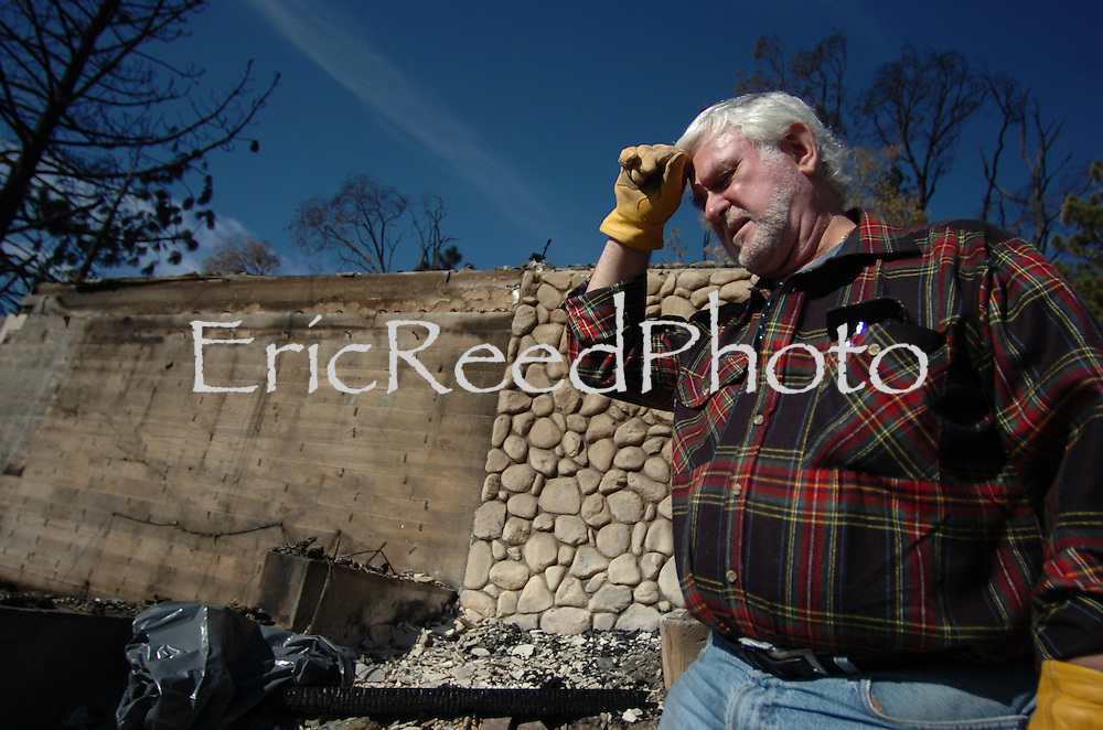 Resident of the Grass Valley Lake area in Lake Arrowhead, Sid Lewis stands in the ashes of his Medera Lane home as many return to their homes to survey the damage and sift through the ashes of the homes lost,  October 30, 2007. Eric Reed Photographer