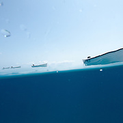 A split shot, with half underwater and half showing a row of small boats tied up behind a larger boat on a calm day on Swains Reef on the southern end of Australia's Great Barrier Reef.