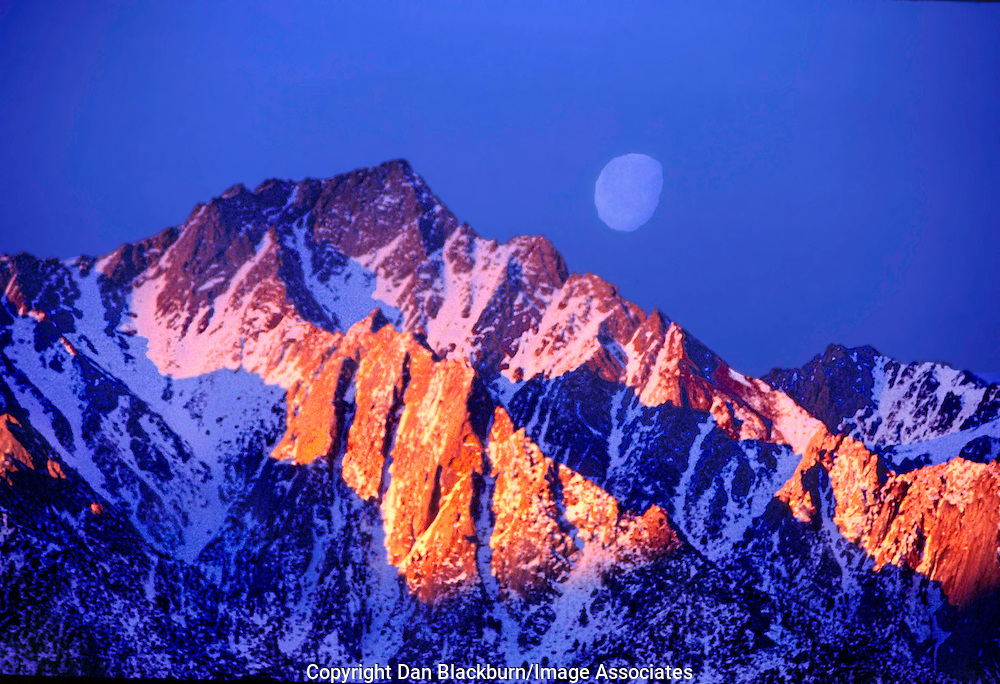 An almost full moon sets behind Lone Pine Peak in the eastern Sierra Nevada range of California while sunrise lights up the prominent peak at the same time.