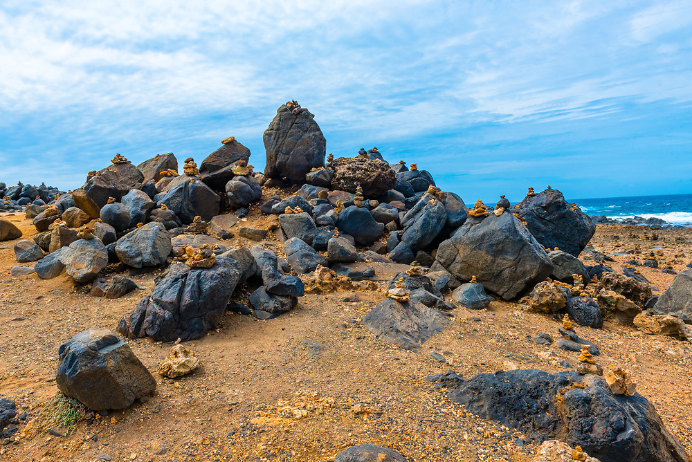 Large rocks topped with mementos cover a beach in Aruba.