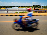 01 JULY 2015 - BANG LUANG, CHAI NAT, THAILAND:  A person rides their motorcycle over the Chao Phraya Dam in Chai Nat province. The reservoir behind the dam is at less than 10 percent of capacity. Central Thailand is contending with drought. By one estimate, about 80 percent of Thailand's agricultural land is in drought like conditions and farmers have been told to stop planting new acreage of rice, the area's principal cash crop. Water in reservoirs are below 10 percent of their capacity, a record low. Water in some reservoirs is so low, water no longer flows through the slipways and instead has to be pumped out of the reservoir into irrigation canals. Farmers who have planted their rice crops are pumping water out of the irrigation canals in effort to save their crops. Homes have collapsed in some communities on the Chao Phraya River, the main water source for central Thailand, because water levels are so low the now exposed embankment is collapsing. This is normally the start of the rainy season, but so far there hasn't been any significant rain.    PHOTO BY JACK KURTZ