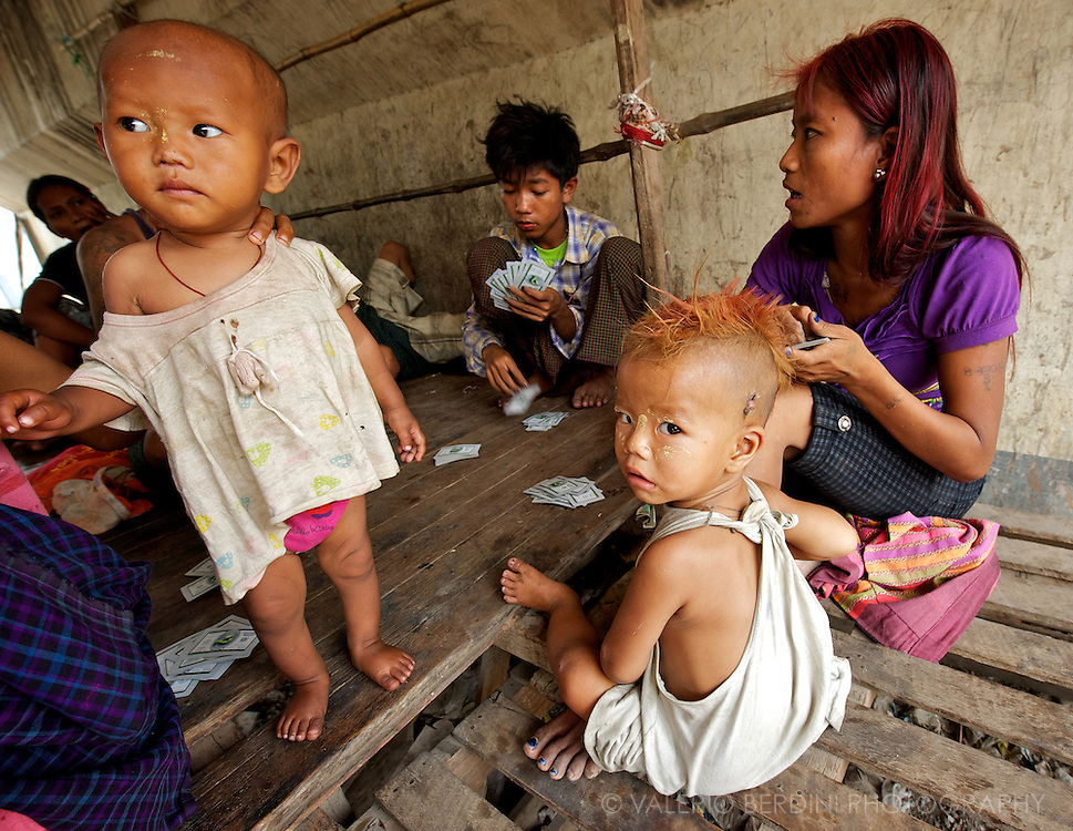 Teenagers with their young sons play cards under a bridge in Mandalay.