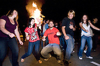 Jonna Clark, Vanessa Moses, Nicolas Richardson, Leland Clark and Sarah Munn dance to the music while the rival's Golden Eagle burns on top of the bonfire at Belmont High School Friday evening to kick off the weekend's Homecoming events.  (Karen Bobotas/for the Laconia Daily Sun)