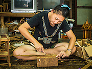 02 NOVEMBER 2016 - BANGKOK, THAILAND:  GOB, who now runs the family spirit house workshop, hand measures small pieces of teak for use on the exterior wall of a spirit house. There used to be 10 families making traditional spirit houses out of teak wood in Ban Fuen, a community near Wat Suttharam in the Khlong San district of Bangkok. The area has been gentrified and many of the spirit house makers have moved out, their traditional wooden Thai houses replaced by modern apartments. Now there is just one family making the elaborate spirit houses. The spirit houses are made by hand. It takes three days to make a small one and up to three weeks to make a large one. Prices start at about $90 (US) for a small one. The largest, most elaborate ones can cost over $1,000 (US). Almost every home and most commercial buildings in Thailand have a spirit house, which is a shrine to the protective spirit of a the land. Spirit houses are also common in Burma, Cambodia, and Laos.       PHOTO BY JACK KURTZ