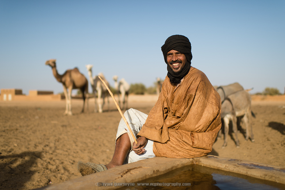 A camel handler taking a break from leading a camel that is used to haul buckets up from a well in Bassikounou, Mauritania on 7 March 2013.