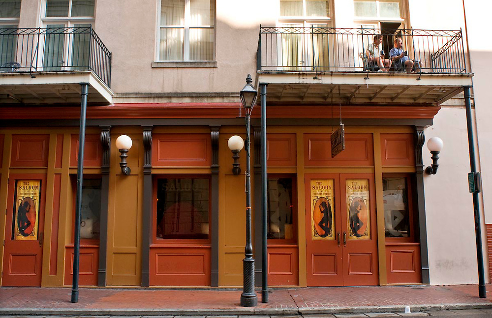 Two men sitting on the balcony above The Saloon, a popular tavern located on Bourbon St. in the French Quarter in New Orleans, LA.